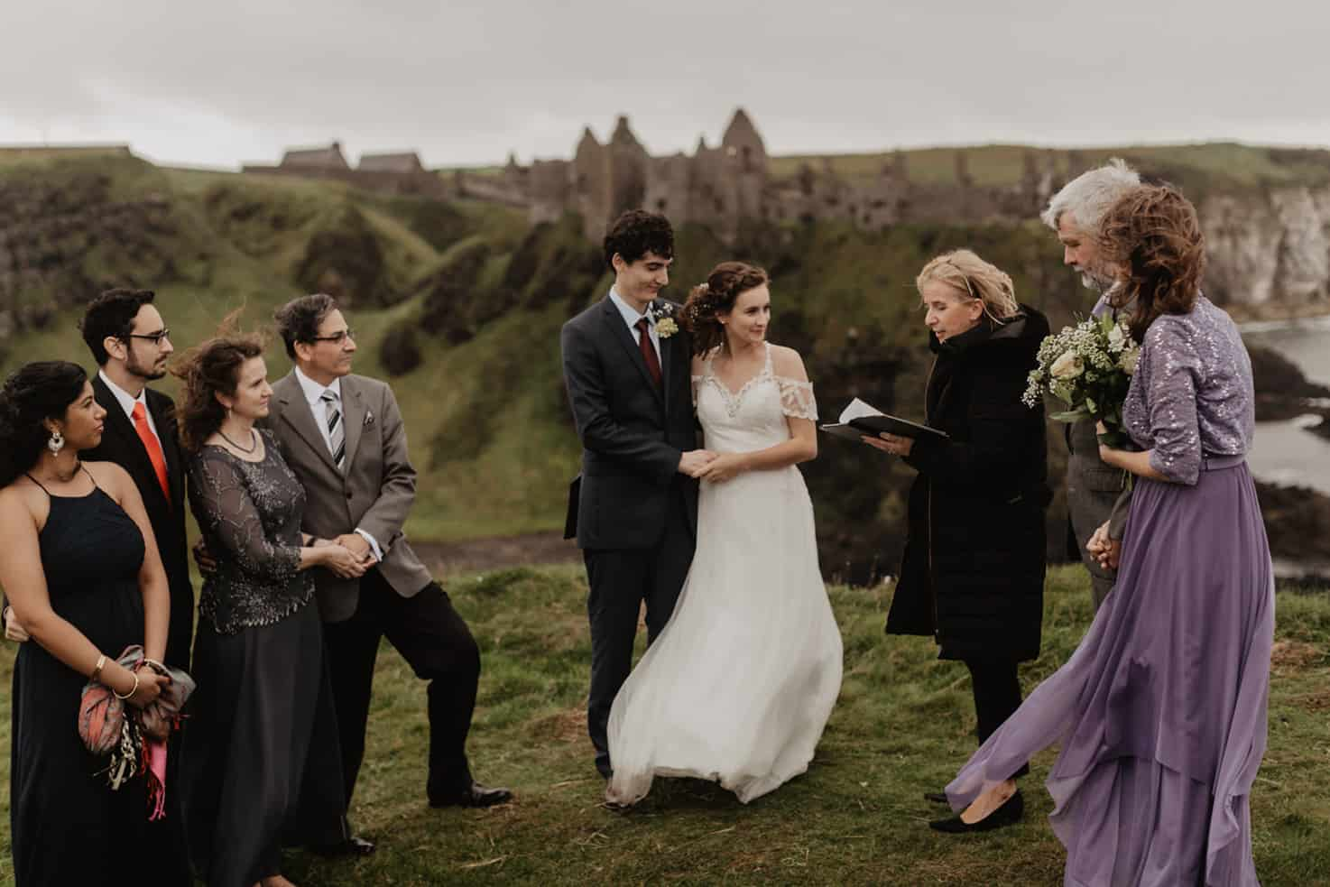 A couple eloping on the cliff tops with their family, over looking Dunluce Castle in Northern Ireland