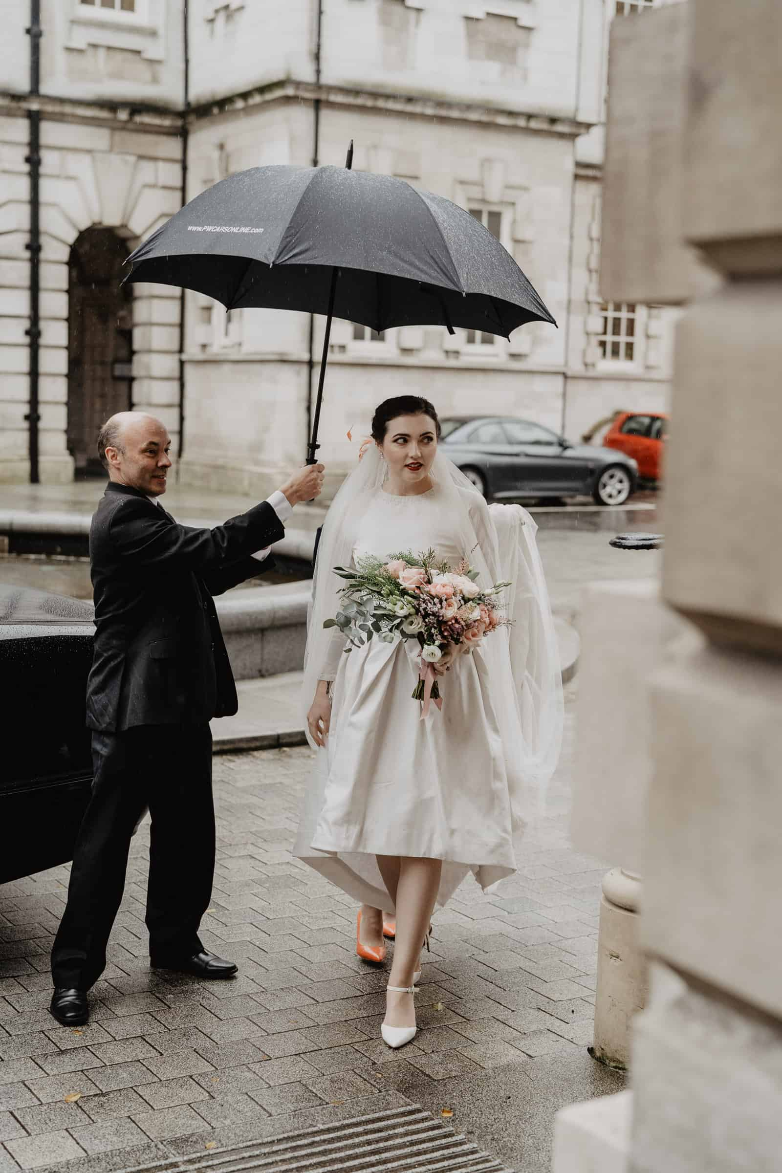 Bride walking into city hall with umbrella covering her